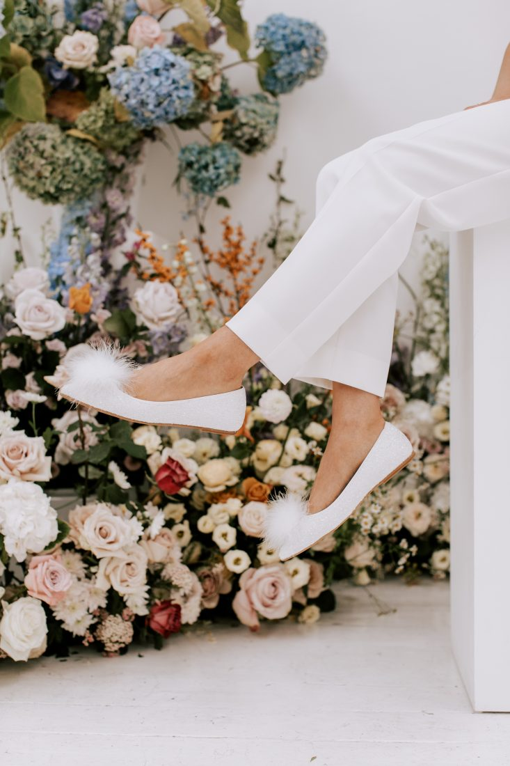 """<a href=""""https://charlottemills.com/collections/wedding-shoes/products/joy"""" target=""""_blank"""" rel=""""noopener noreferrer"""">Joy Pearl Pom Pom by Charlotte Mills</a> £220"""
